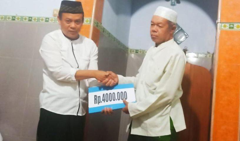 H. Ihsaudin yang juga Kepala Desa Bogoran menyerahkan infaq kepada Ketua Ranting NU Bogoran di sela Lailatul Ijtima', Ahad (12/1/2020).