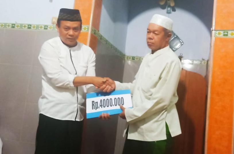 H. Ihsanudin yang juga Kepala Desa Bogoran menyerahkan infaq kepada Ketua Ranting NU Bogoran di sela Lailatul Ijtima', Ahad (12/1/2020).